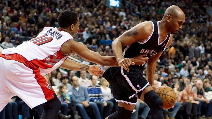 Toronto Raptors guard DeMar DeRozan (10) fouls Brooklyn Nets forward Jerry Stackhouse during the first half of an NBA basketball game in Toronto, Sunday, April 14, 2013. (AP Photo/The Canadian Press, Frank Gunn)