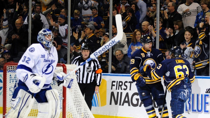 Tampa Bay Lightning goaltender Mathieu Garon (32) reacts to a celebration by Buffalo Sabres centers Cody Hodgson (19) and Tyler Ennis (63) after a goal by Ennis during the first period of an NHL hockey game in Buffalo, N.Y., Sunday, April 14, 2013. (AP Photo/Gary Wiepert)