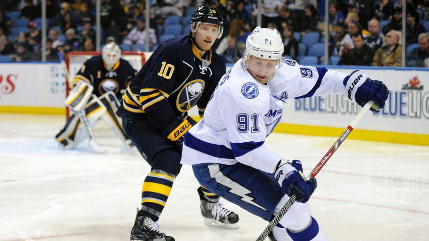 Buffalo Sabres' Christian Ehrhoff (10), of Germany, defends as Tampa Bay Lightning's Steve Stamkos (91) handles the puck during the second period of an NHL hockey game in Buffalo, N.Y., Sunday, April 14, 2013. (AP Photo/Gary Wiepert)