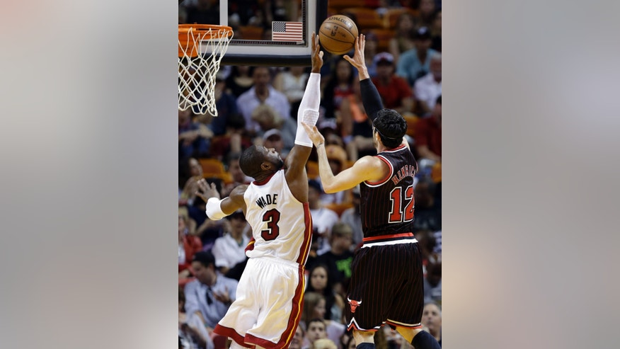 Chicago Bulls' Kirk Hinrich (12) shoots as Miami Heat's Dwyane Wade (3) defends during the first half of an NBA basketball game on Sunday, April 14, 2013, in Miami. (AP Photo/Lynne Sladky)