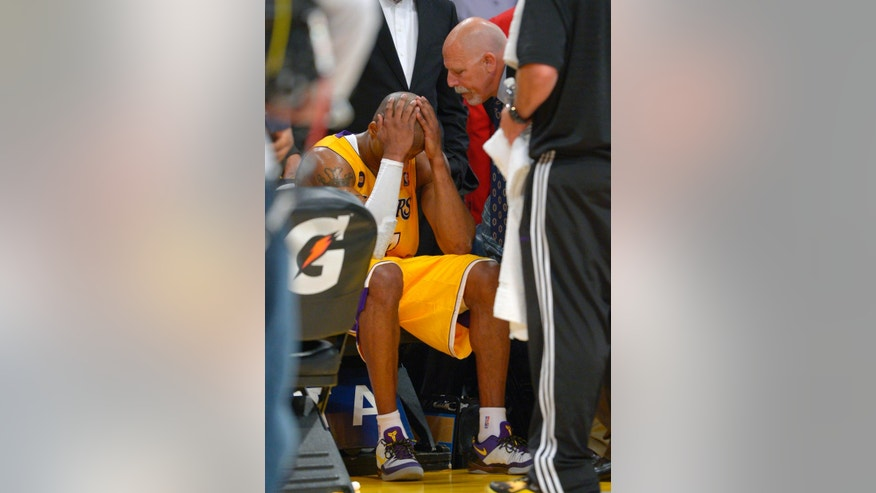 Los Angeles Lakers guard Kobe Bryant, left, puts his head in his hands as trainer Gary Vitti looks on after being injured during the second half of their NBA basketball game against the Golden State Warriors, Friday, April 12, 2013, in Los Angeles. The Lakers won 118-116. (AP Photo/Mark J. Terrill)