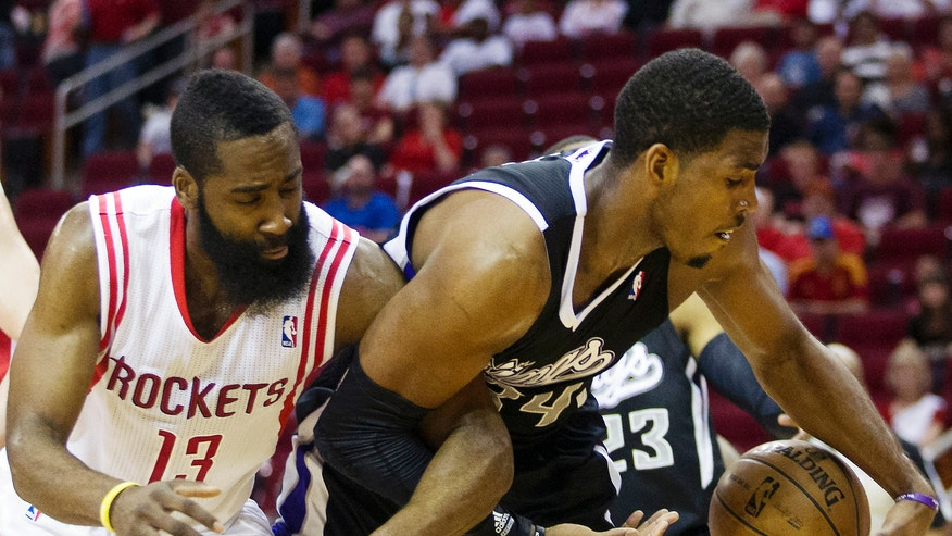 Houston Rockets guard James Harden (13) and Sacramento Kings forward Jason Thompson (34) get tangled up during the second half of an NBA basketball game, Sunday, April 14, 2013, in Houston. The Rockets won 121-100. (AP Photo/Patric Schneider)