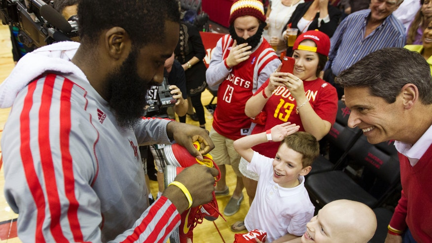 Houston Rockets guard James Harden gives Patrick DeClaire, 9, bottom right, and his twin brother Trent his shoes after an NBA basketball game against the Sacramento Kings, Sunday, April 14, 2013, in Houston. Patrick, who has stage 4 neuroblastoma, has previously been visited by the Rockets and sat courtside for the game. The Rockets won 1221-100. (AP Photo/ Patric Schneider)