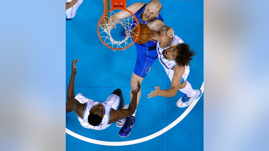 Dallas Mavericks center Chris Kaman, top, New Orleans Hornets center Robin Lopez, right, and  forward Al-Farouq Aminu, bottom, battle for a rebound during the first half of an NBA basketball game in New Orleans, Sunday, April 14, 2013. (AP Photo/Jonathan Bachman)