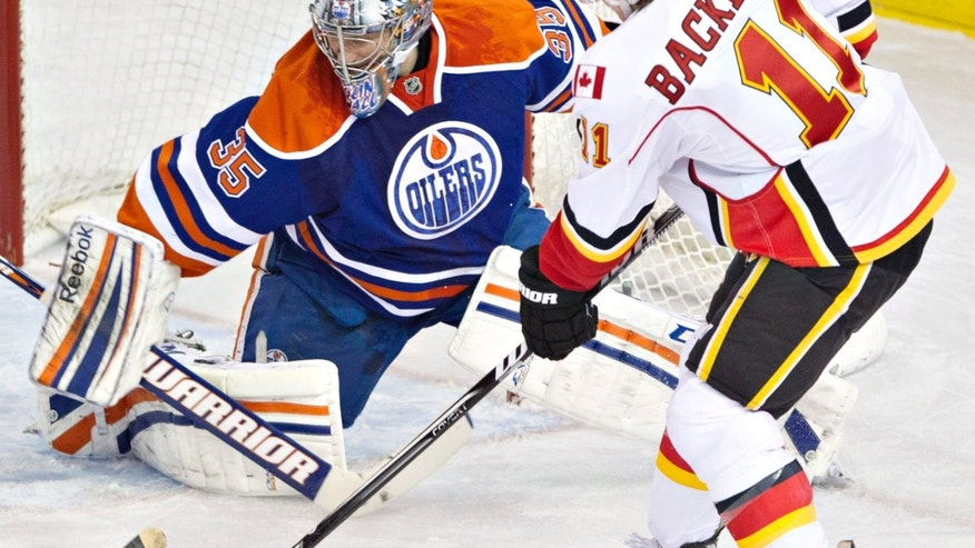 Calgary Flames' Mikael Backlund, right, is stopped by Edmonton Oilers goalie Nikolai Khabibulin, left, during first-period NHL hockey game action in Edmonton, Alberta, Saturday, April 13, 2013. (AP Photo/The Canadian Press, Jason Franson)