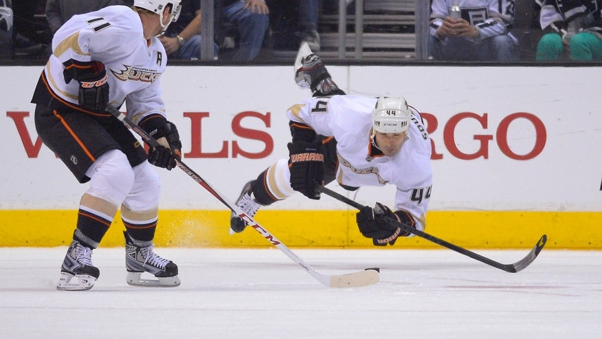 Anaheim Ducks defenseman Sheldon Souray, right, falls as he skates with the puck as center Saku Koivu, of Finland, looks on during the first period of their NHL hockey game against the Los Angeles Kings, Saturday, April 13, 2013, in Los Angeles. (AP Photo/Mark J. Terrill)