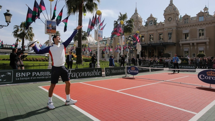 Novak Djokovic of Serbia serves the ball to Andy Murray of Britain during an exhibition match, in front of the Casino of Monte-Carlo, in Monaco, Saturday, April 13, 2013, during the Monte Carlo Tennis Masters tournament. (AP Photo/Lionel Cironneau)