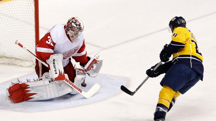 Detroit Red Wings goalie Jimmy Howard (35) blocks a shot by Nashville Predators right wing Matt Halischuk (24) in the second period of an NHL hockey game, Sunday, April 14, 2013, in Nashville, Tenn. (AP Photo/Mark Humphrey)