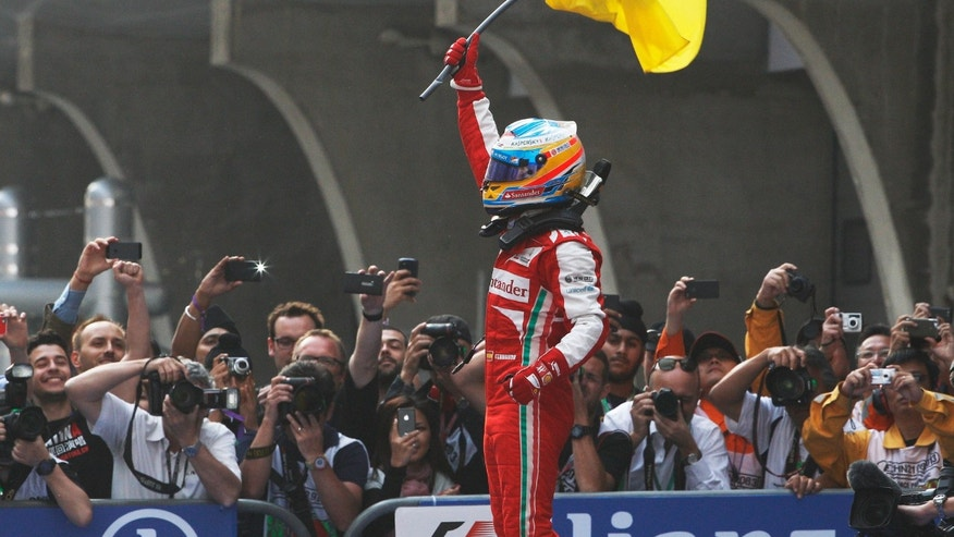 Ferrari driver Fernando Alonso of Spain celebrates after winning the Chinese Formula One Grand Prix in Shanghai, China Sunday, April 14, 2013. (AP Photo/Greg Baker)