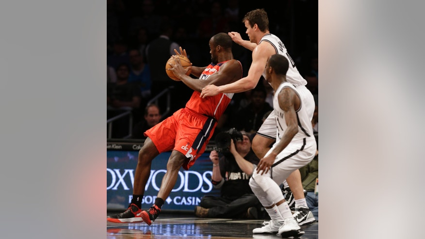 Washington Wizards center Emeka Okafor (50) loses his balance trying to stay in bounds as he defends Brooklyn Nets guard Tyshawn Taylor (41) and Nets forward Kris Humphries (43) in the first half of their their NBA basketball game, Monday, April 15, 2013, in New York. (AP Photo/Kathy Willens)