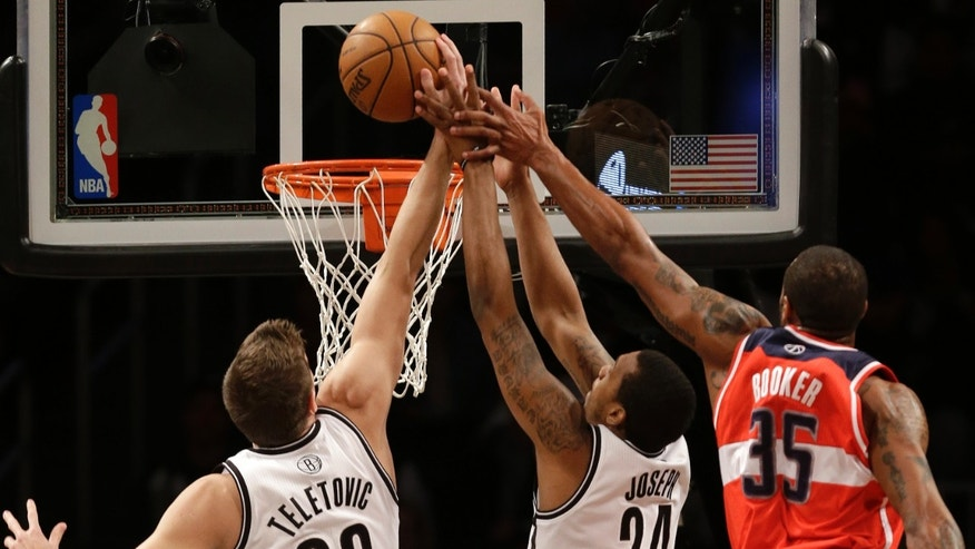 Brooklyn Nets forwards Mirza Teletovic (33) and Kris Joseph (24) defend Washington Wizards forward Trevor Booker (35) in the first half of their their NBA basketball game, Monday, April 15, 2013, in New York. (AP Photo/Kathy Willens)
