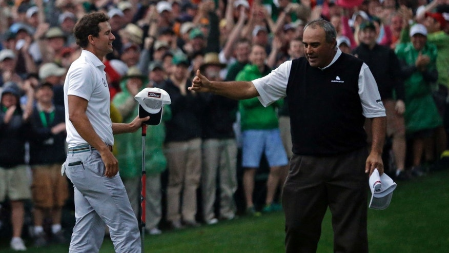 Angel Cabrera, of Argentina, gives Adam Scott, of Australia, a thumbs up after Scott made a birdie putt on the second playoff hole to win the Masters golf tournament Sunday, April 14, 2013, in Augusta, Ga. (AP Photo/David J. Phillip)