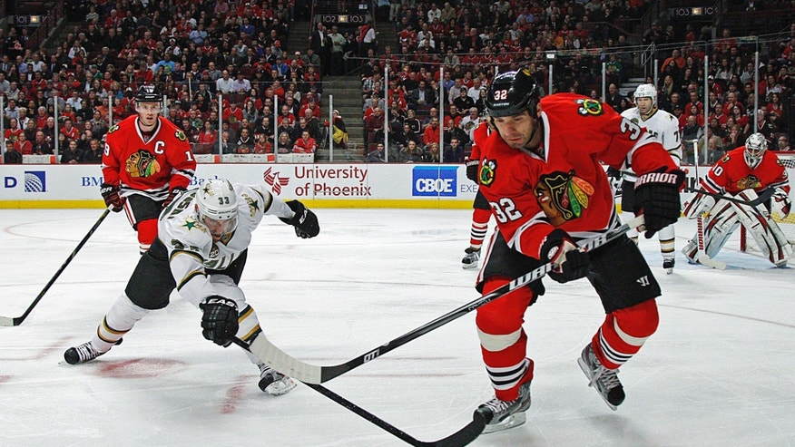 Chicago Blackhawks' Michal Rozsival tries to outrace  Dallas Stars' Alex Goligoski to the puck during the first period in an NHL hockey game in Chicago, Monday, April 15, 2013. (AP Photo/Charles Cherney)