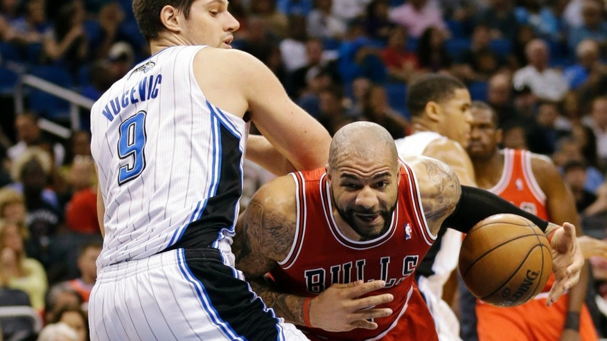Chicago Bulls' Carlos Boozer, right, makes a move to the basket past Orlando Magic's Nikola Vucevic (9), of Montenegro, during the first half of an NBA basketball game, Monday, April 15, 2013, in Orlando, Fla. (AP Photo/John Raoux)