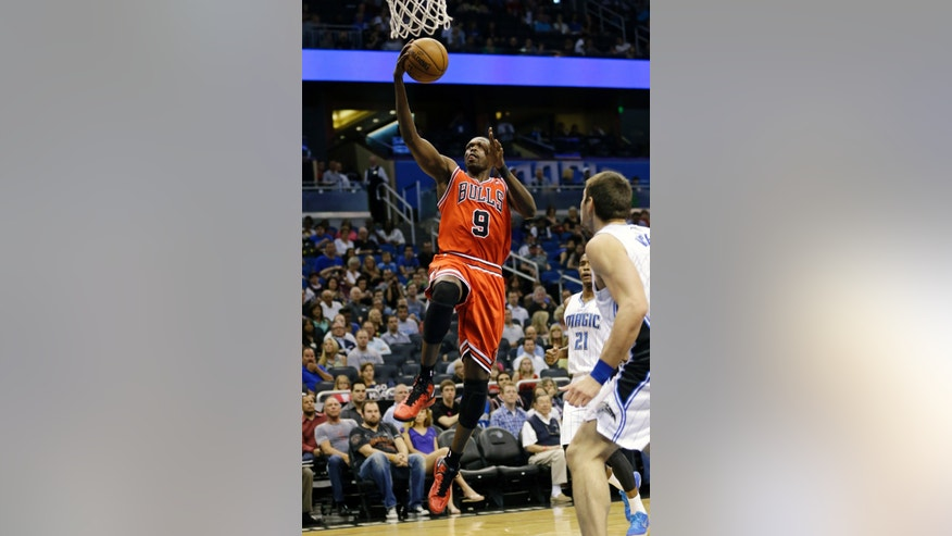 Chicago Bulls' Luol Deng (9)  drives to the basket past Orlando Magic's Maurice Harkless (21) and Nikola Vucevic, right, of Montenegro, during the first half of an NBA basketball game, Monday, April 15, 2013, in Orlando, Fla. (AP Photo/John Raoux)