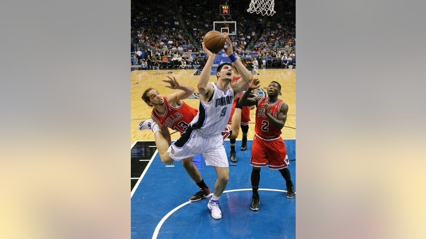 Orlando Magic's Nikola Vucevic (9), of Montenegro, shoots after getting around Chicago Bulls' Joakim Noah (13) and Nate Robinson (2) during the first half of an NBA basketball game, Monday, April 15, 2013, in Orlando, Fla. (AP Photo/John Raoux)