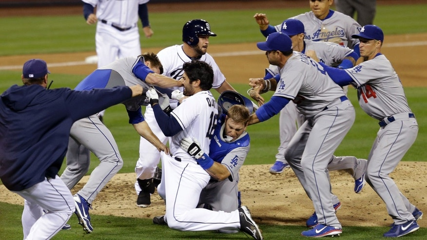 San Diego Padres' Carlos Quentin charges into Los Angeles Dodgers pitcher Zack Greinke after being hit by a pitch in the sixth inning of baseball game in San Diego, on April 11, 2013.