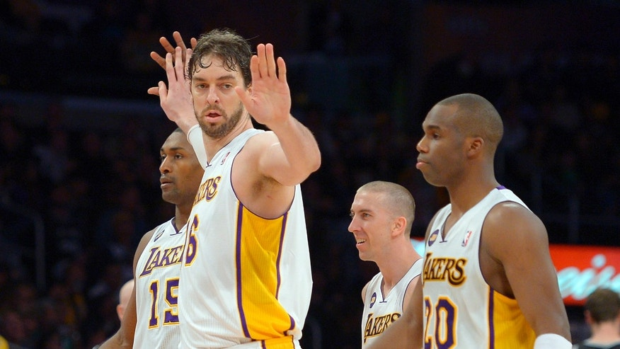 Los Angeles Lakers forward Pau Gasol, second from left, of Spain, is congratulated by forward Metta World Peace, left, as guard Steve Blake, second from right, and guard Jodie Meeks looks on during the second half of their NBA basketball game, Sunday, April 14, 2013, in Los Angeles. The Lakers won 91-86. (AP Photo/Mark J. Terrill)