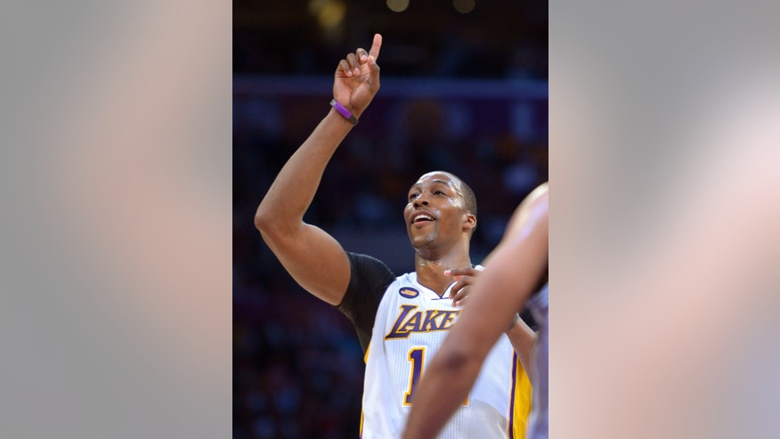 Los Angeles Lakers center Dwight Howard points to the sky after making a free throw during the second half of their NBA basketball game against the San Antonio Spurs, Sunday, April 14, 2013, in Los Angeles. The Lakers won 91-86. (AP Photo/Mark J. Terrill)