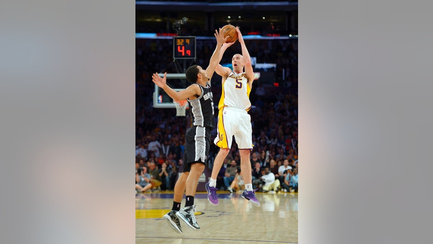 Los Angeles Lakers guard Steve Blake, right, shoots as San Antonio Spurs guard Cory Joseph defends during the second half of their NBA basketball game, Sunday, April 14, 2013, in Los Angeles. Blake scored 23 points as the Lakers won 91-86. (AP Photo/Mark J. Terrill)