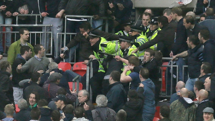 Police officers raise their battens as they control the crowd as Millwall play Wigan Athletic during their English FA Cup semifinal soccer match at Wembley stadium in London, Saturday, April  13, 2013. (AP Photo/Alastair Grant)