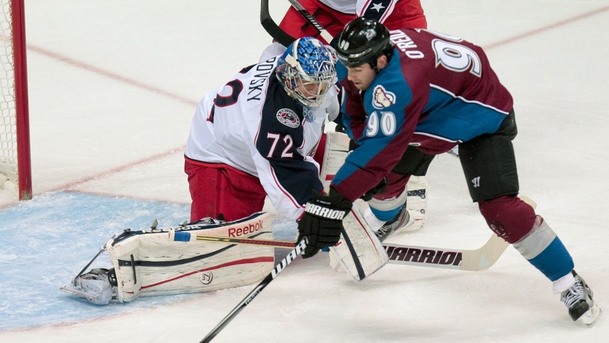 Colorado Avalanche's  Ryan O'Reilly (90) can't get a shot off around Columbus Blue Jackets goalie Sergei Bobrovsky (72), of Russia, during the first period of an NHL hockey game on Monday, April 15, 2013 in Denver. (AP Photo/Barry Gutierrez)