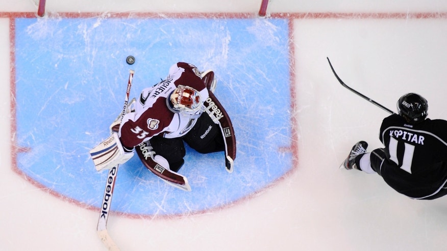 Los Angeles Kings center Anze Kopitar, right, of Slovenia, scores on Colorado Avalanche goalie Jean-Sebastien Giguere during an overtime shootout in their NHL hockey game, Thursday, April 11, 2013, in Los Angeles. The Kings won 3-2 after an overtime shootout. (AP Photo/Mark J. Terrill)