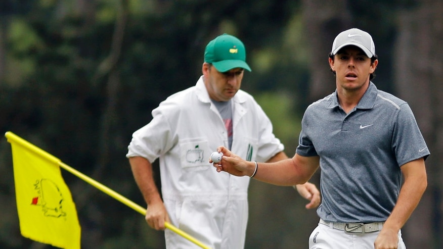 Rory McIlroy, of Northern Ireland, holds up his ball after putting on the third green during the fourth round of the Masters golf tournament Sunday, April 14, 2013, in Augusta, Ga. Left is his caddie J.P. Fitzgerald. (AP Photo/Matt Slocum)