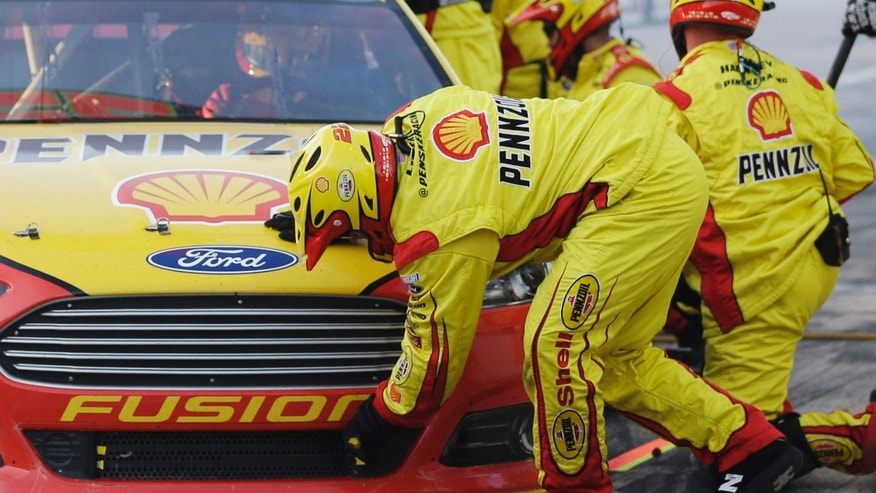 Joey Logano has adjustments made to his car at a pit stop during the NASCAR Sprint Cup series NRA 500 auto race at Texas Motor Speedway, Saturday, April 13, 2013, in Fort Worth, Texas. (AP Photo/Tony Gutierrez)