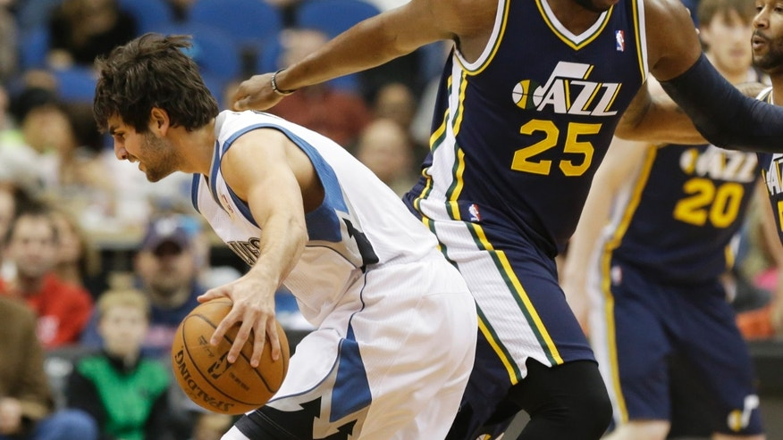 Minnesota Timberwolves' Ricky Rubio, left, assumes a low profile around Utah Jazz's Al Jefferson of Spain in the first quarter of an NBA basketball game Monday, April 15, 2013 in Minneapolis. (AP Photo/Jim Mone)