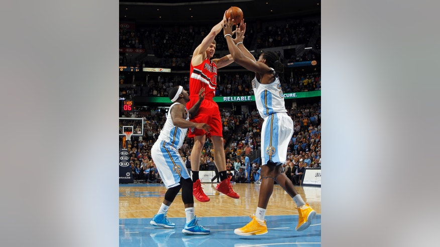 Portland Trail Blazers center Meyers Leonard, center, jumps to shoot over Denver Nuggets guard Ty Lawson, left, and forward Kenneth Faried in the first quarter of an NBA basketball game in Denver, Sunday, April 14, 2013. (AP Photo/David Zalubowski)