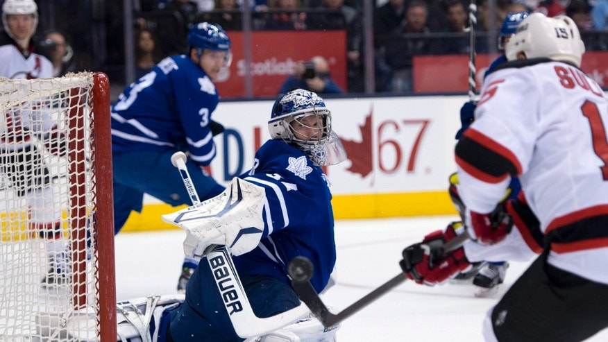 Toronto Maple Leafs goaltender James Reimer makes a save on New Jersey Devils left winger Steve Sullivan, right, during the first period of their NHL hockey game in Toronto, Monday, April 15, 2013. (AP Photo/The Canadian Press, Frank Gunn)