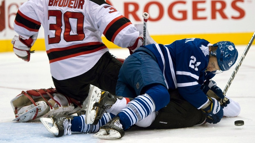 New Jersey Devils goaltender Martin Brodeur (30) goes down to make a save as the puck bounces off Toronto Maple Leafs left winger James van Riemsdyk during the second period of their NHL hockey game in Toronto, Monday, April 15, 2013. (AP Photo/The Canadian Press, Frank Gunn)