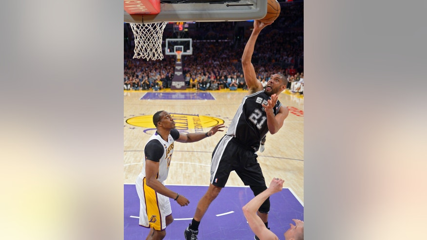San Antonio Spurs forward Tim Duncan, puts up a shot as Los Angeles Lakers center Dwight Howard looks on during the second half of their NBA basketball game, Sunday, April 14, 2013, in Los Angeles. The Lakers won 91-86. (AP Photo/Mark J. Terrill)