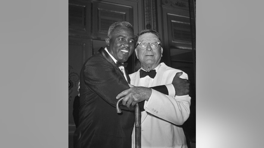 "FILE - In this July 20, 1962 file photo, baseball player Jackie Robinson embraces Branch Rickey in New York. Rickey was general manager of the Brooklyn Dodgers when Robinson was hired. The home area of the late baseball executive Rickey expects increased interest in his southern Ohio roots from his depiction in the movie ""42,"" in which Harrison Ford plays the man who signed Jackie Robinson to challenge baseball's color line. (AP Photo/File)"