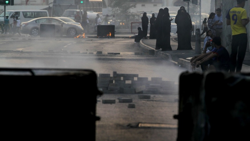 Bahraini anti-government protesters block a road with burning debris to slow approaching riot police in Sanabis, Bahrain, Monday, April 15, 2013. The race is to be held Sunday. Bahrain's government has backed proposals to impose penalties of up five years in prison for insulting the Gulf state's king or its national symbols, the media said Monday. (AP Photo/Hasan Jamali)