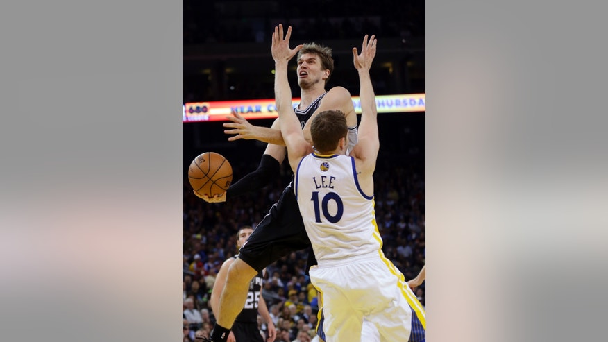 San Antonio Spurs' Tiago Splitter, top, drives to the basket as Golden State Warriors' David Lee (10) defends during the first half of an NBA basketball game in Oakland, Calif., Monday, April 15, 2013. (AP Photo/Marcio Jose Sanchez)