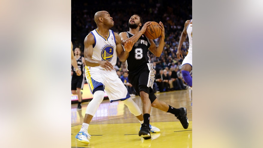 San Antonio Spurs' Patty Mills (8) dribbles to the basket as Golden State Warriors' Jarrett Jack (2) defends during the first half of an NBA basketball game in Oakland, Calif., Monday, April 15, 2013. (AP Photo/Marcio Jose Sanchez)