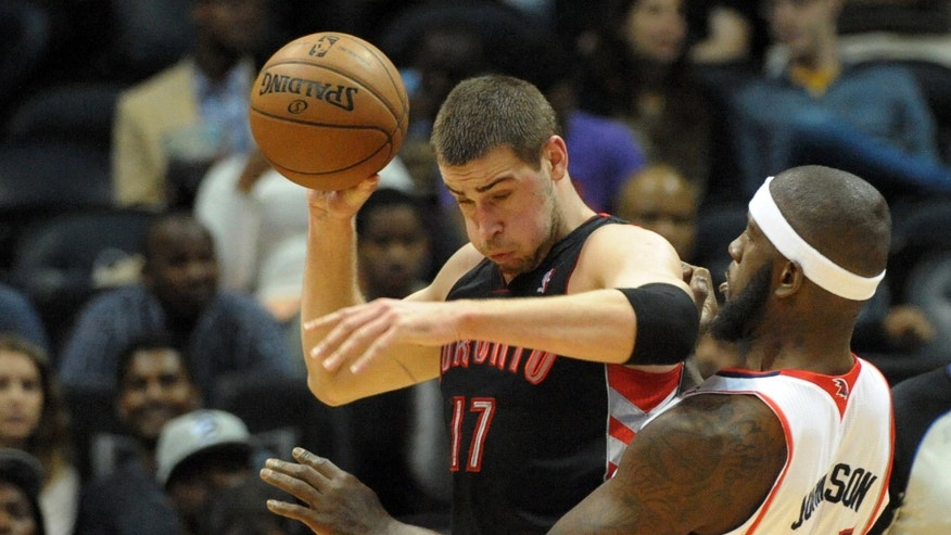 Toronto Raptors' Jonas Valanciunas (17), of Lithuania, pushes back against Atlanta Hawks' Ivan Johnson in the first half of an NBA basketball game, Tuesday, April 16, 2013, in Atlanta. (AP Photo/David Tulis)