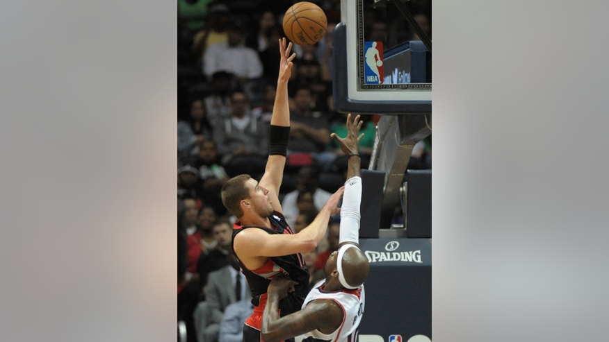Toronto Raptors' Jonas Valanciunas (17), of Lithuania, shoots over Atlanta Hawks' Johan Petro, of France, in the first half of an NBA basketball game, Tuesday, April 16, 2013, in Atlanta. (AP Photo/David Tulis)