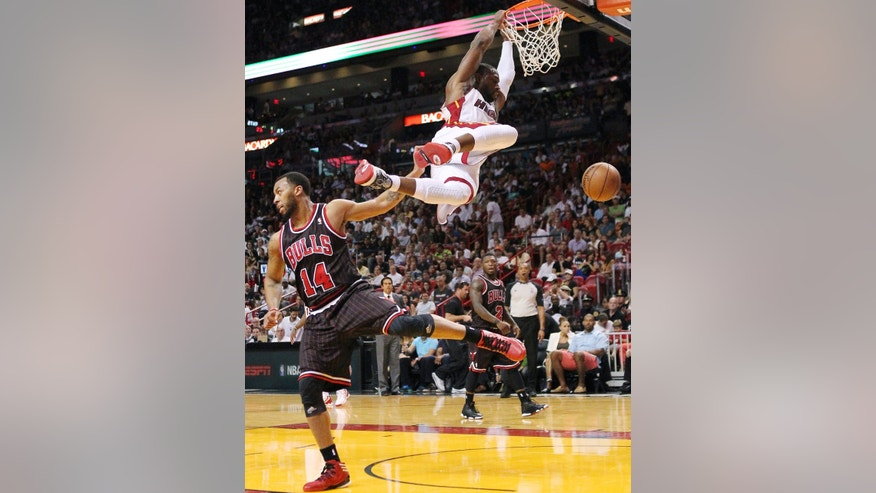 Miami Heat's Dwyane Wade dunks over Chicago Bulls' Daequan Cook (14) during the second quarter of an NBA basketball game in Miami, Sunday, April 14, 2013. The Heat won 105-93. (AP Photo/El Nuevo Herald, David Santiago)  MAGS OUT