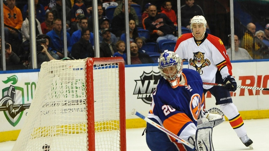 New York Islanders goalie Evgeni Nabokov (20) and Florida Panthers' Tomas Fleischmann (14) watch the puck shot by Panthers' Dmitry Kulikov fly in to the net to score in the first period of an NHL hockey game on Tuesday, April 16, 2013, at Nassau Coliseum in Uniondale, N.Y. (AP Photo/Kathy Kmonicek)