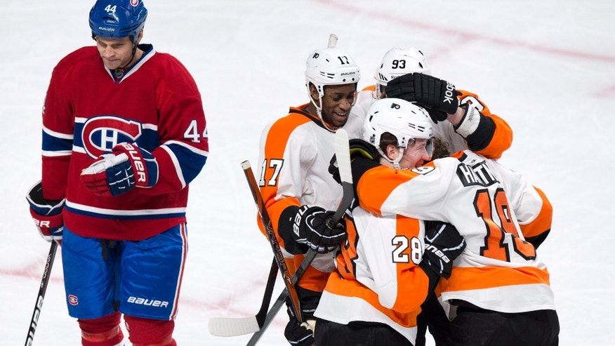 Philadelphia Flyers' Scott Hartnell, right, is congratulated by Wayne Simmonds (17), Claude Giroux (28) and Jakub Voracek (93) for his goal as Montreal Canadiens' Davis Drewiske skates by during the second period of their NHL hockey game, Monday, April 15, 2013, in Montreal. (AP Photo/The Canadian Press, Paul Chiasson)