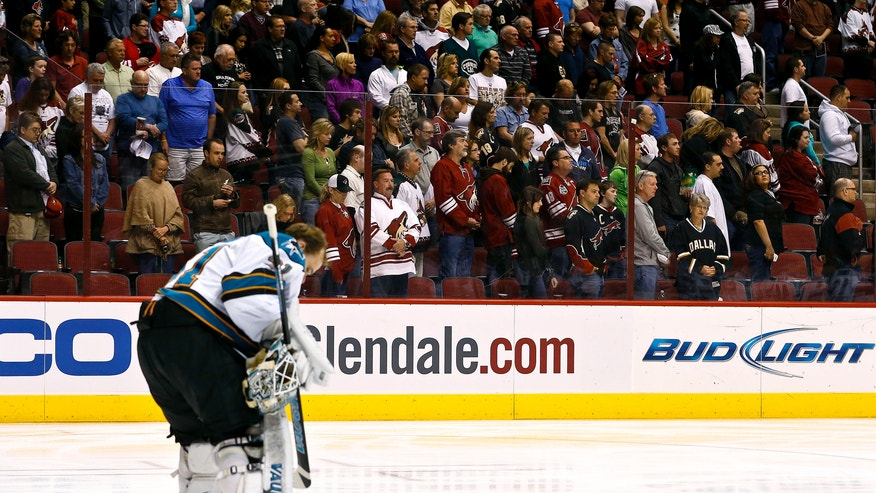 San Jose Sharks' Antti Niemi, of Finland, pauses as fans stand in the background for a moment of silence for the victims of the bombing at the Boston Marathon prior to an NHL hockey game between the Sharks and the Phoenix Coyotes, on Monday, April 15, 2013 in Glendale, Ariz. (AP Photo/Ross D. Franklin)