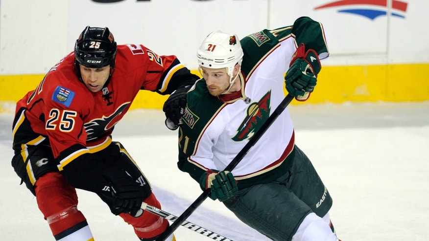 Minnesota Wild's' Kyle Brodziak, right, battles with Calgary Flames' Steve Begin during the second period of an NHL hockey game in Calgary, Alberta, Monday, April 15, 2013. (AP Photo/The Canadian Press, Larry MacDougal)