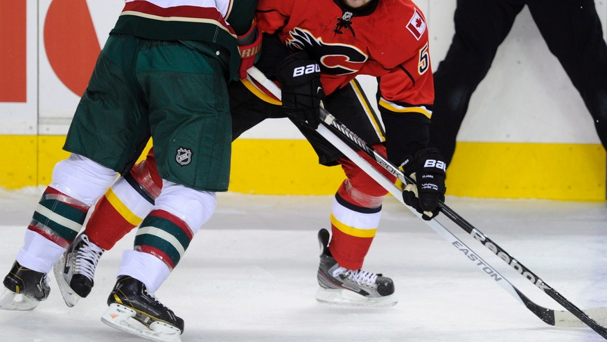 Minnesota Wild's' Brett Clark, left, runs into Calgary Flames' Roman Horak, of the Czech Republic, during the first period of their NHL hockey game in Calgary, Alberta, Monday, April 15, 2013. (AP Photo/The Canadian Press, Larry MacDougal)