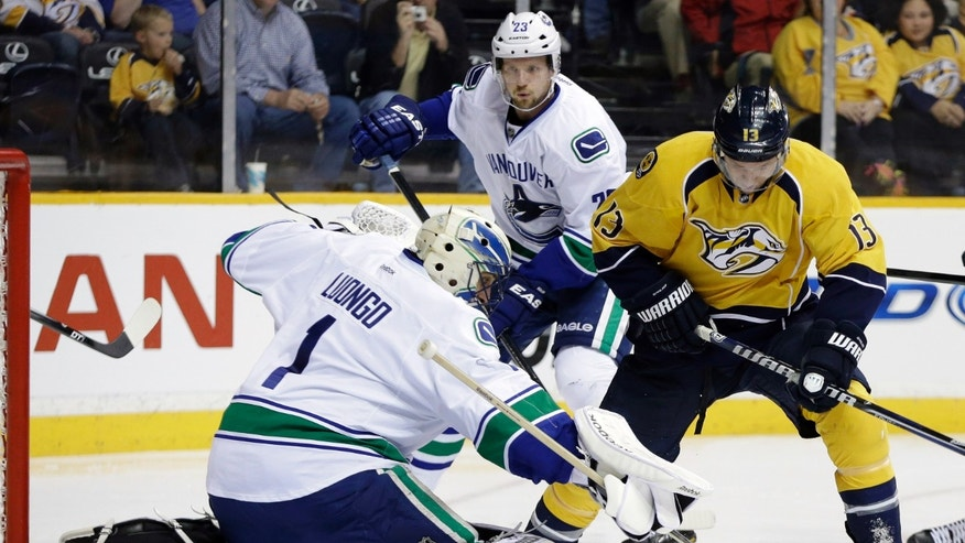Vancouver Canucks goalie Roberto Luongo (1) blocks a shot as Nashville Predators center Nick Spaling (13) watches for the rebound in the second period of an NHL hockey game on Monday, April 15, 2013, in Nashville, Tenn. Behind them is Canucks defenseman Alexander Edler (23), of Sweden. (AP Photo/Mark Humphrey)