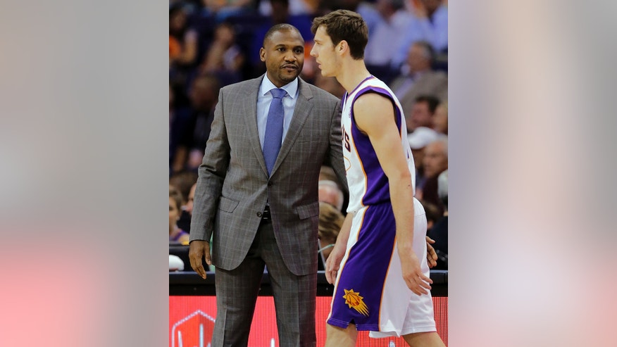 Phoenix Suns head coach Lindsey Hunter talks with Goran Dragic, of Slovenia, during the first half of an NBA basketball game, Monday, April 15, 2013, in Phoenix. (AP Photo/Matt York)