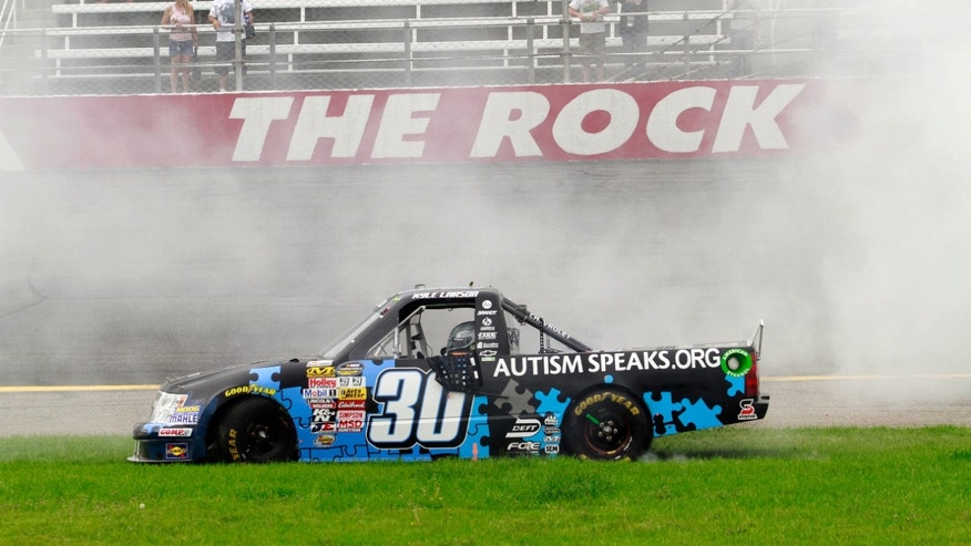 Kyle Larson (30) does a burnout after winning the NASCAR Camping World Truck Series auto race in Rockingham, N.C., Sunday, April 14, 2013. (AP Photo/Jim R. Bounds)