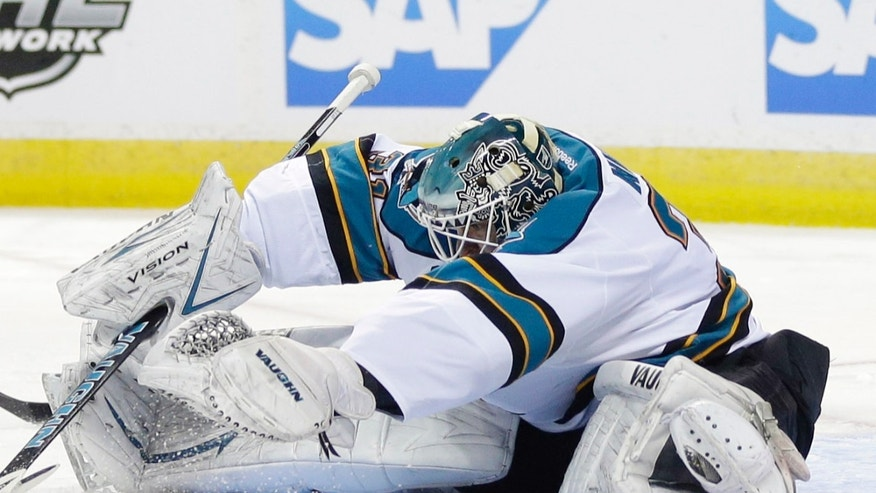 San Jose Sharks goalie Antti Niemi, of Finland, reaches in to stop a shot against the Los Angeles Kings during the second period of an NHL hockey game in San Jose, Calif., Tuesday, April 16, 2013. (AP Photo/Marcio Jose Sanchez)